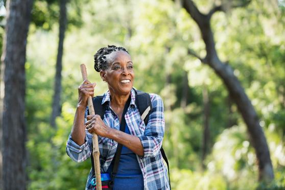 A senior African-American woman in her 70s hiking in a park smiling and leaning on a walking stick, standing with trees and lush foliage in the background.