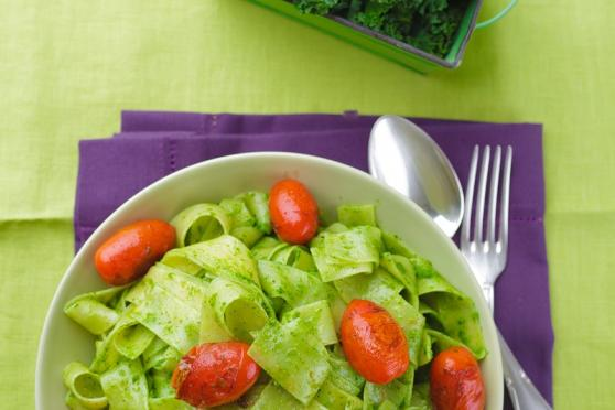Bowl of kale pesto pasta salad, on a napkin with a fork and spoon.